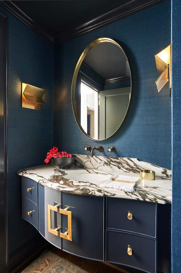 deep blue vanity gold finish circle mirror black and white marble countertop built in wall sconce