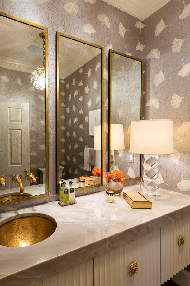 custom light grey neutral toned bathroom with three gold rimmed rectangular mirrors and gold sink