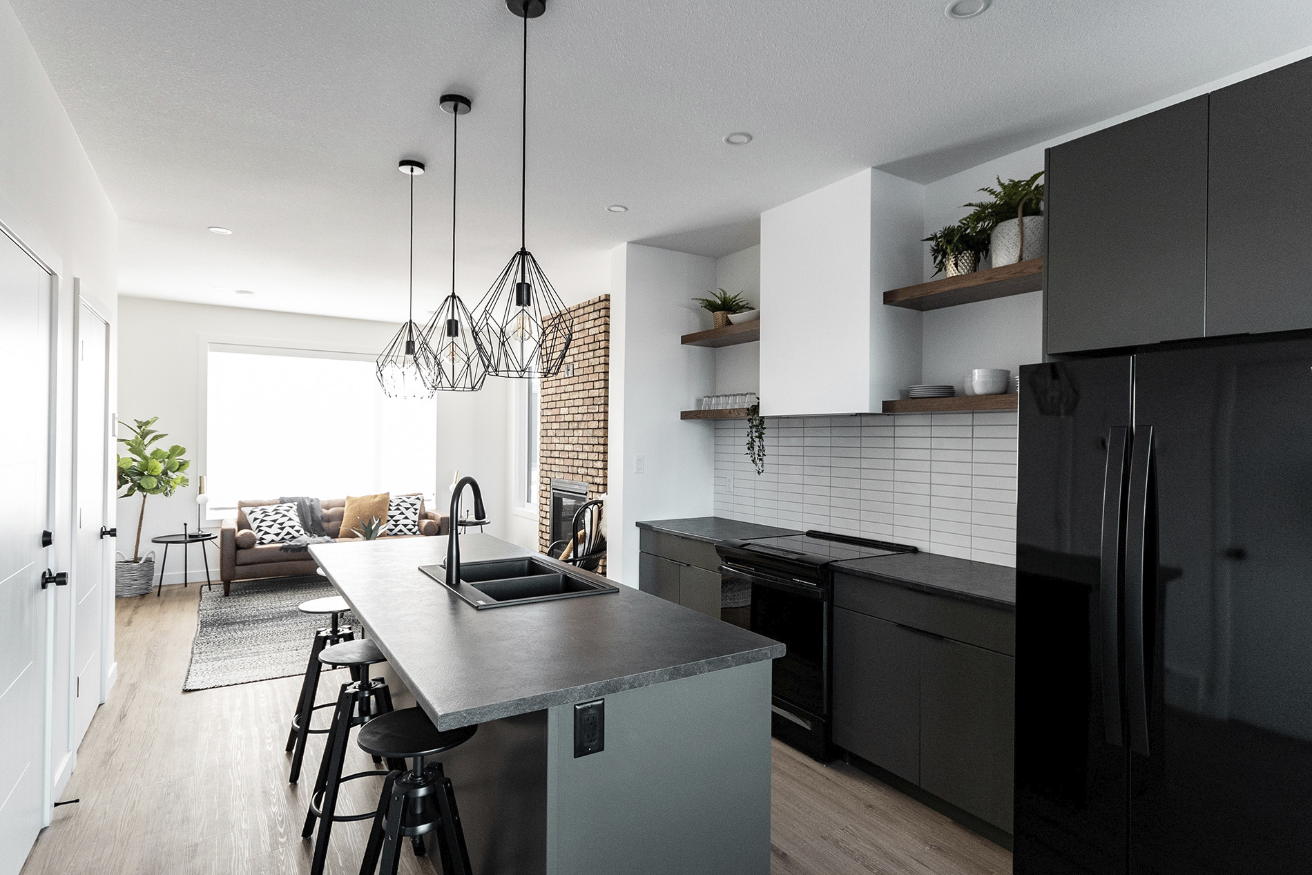 custom kitchen with black finishes white walls with minimalist shelving and custom light fixtures over island