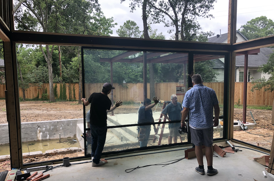 workers installing window into frame of house
