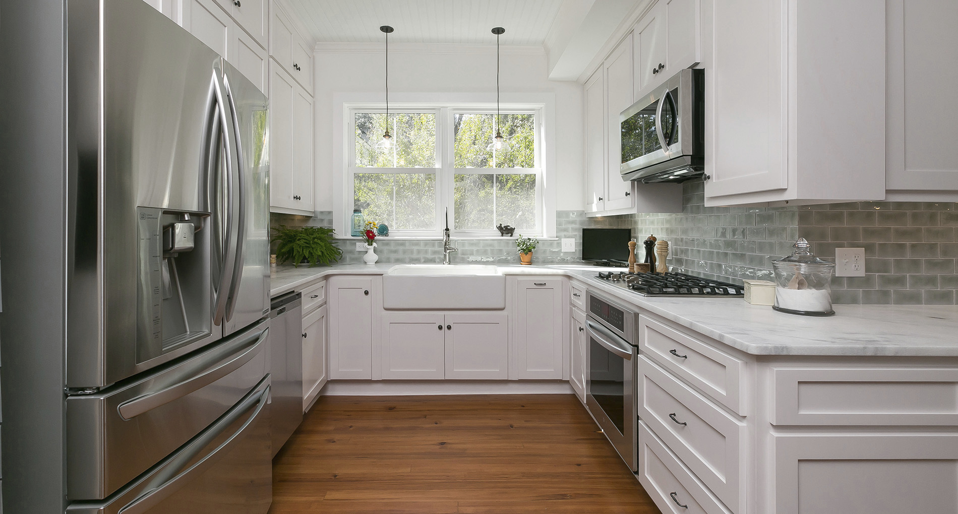 Custom kitchen with trough sink, mint backsplash and white cabinets