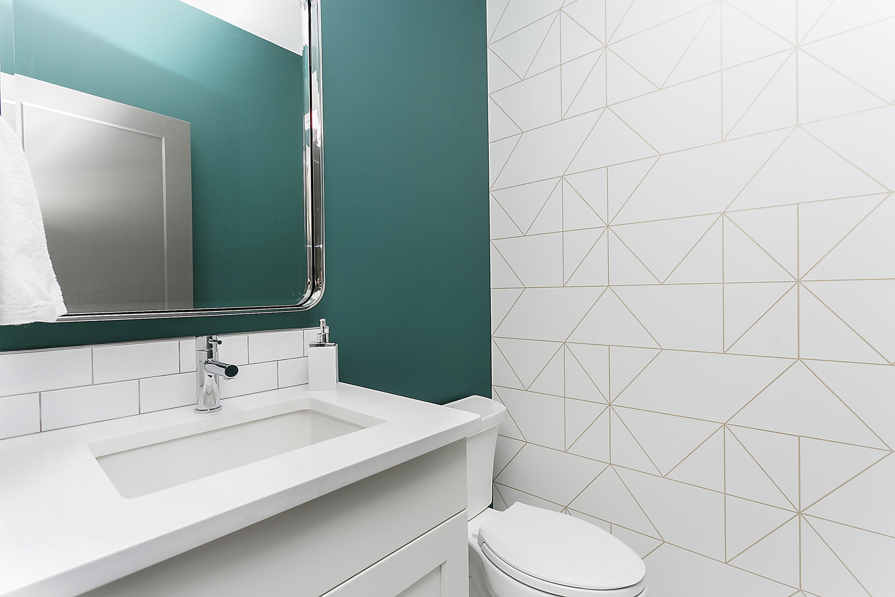 bathroom with sink against teal wall and geometric gold pattern on white wallpaper on feature wall
