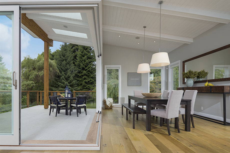 custom home with oak colored luxury vinyl flooring in dining area with access to outdoor patio with table