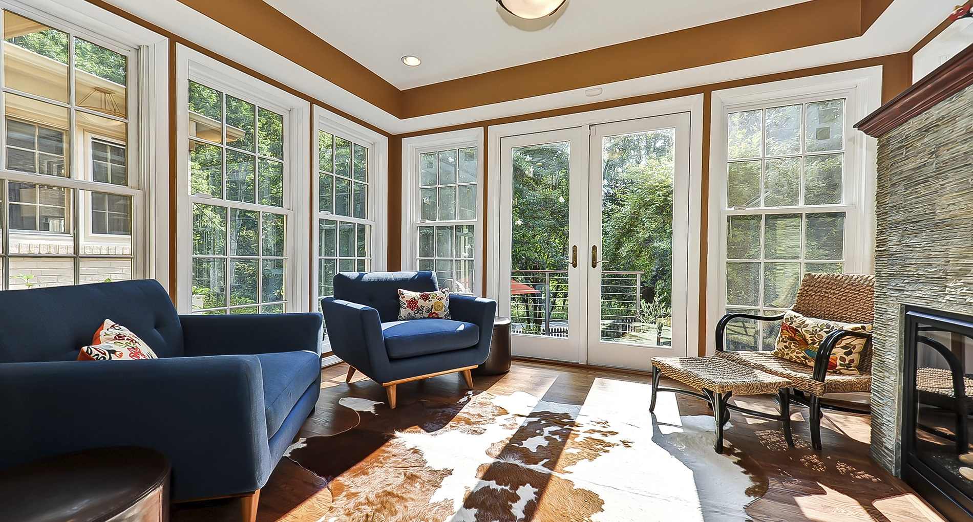 enclosed sun room with animal hide rug blue chairs