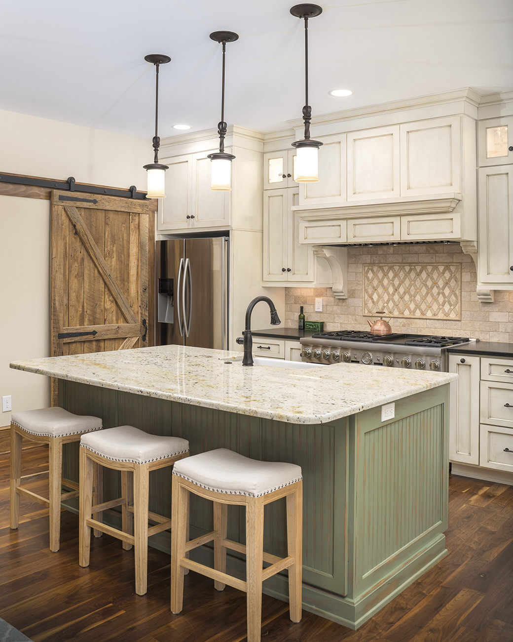 custom kitchen with natural wooden sliding pantry doors and green island