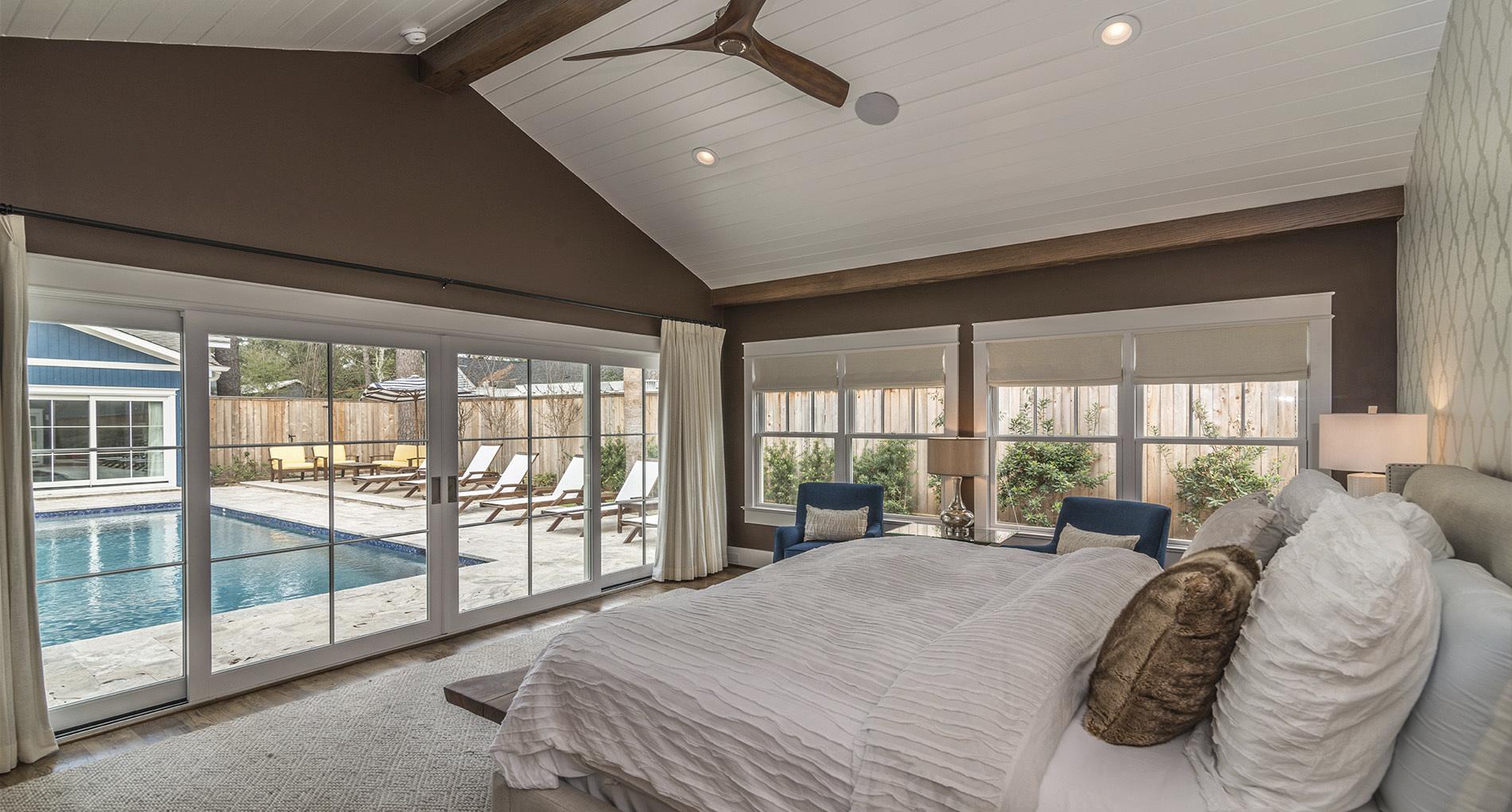 bedroom with floor to ceiling windows overlooking pool