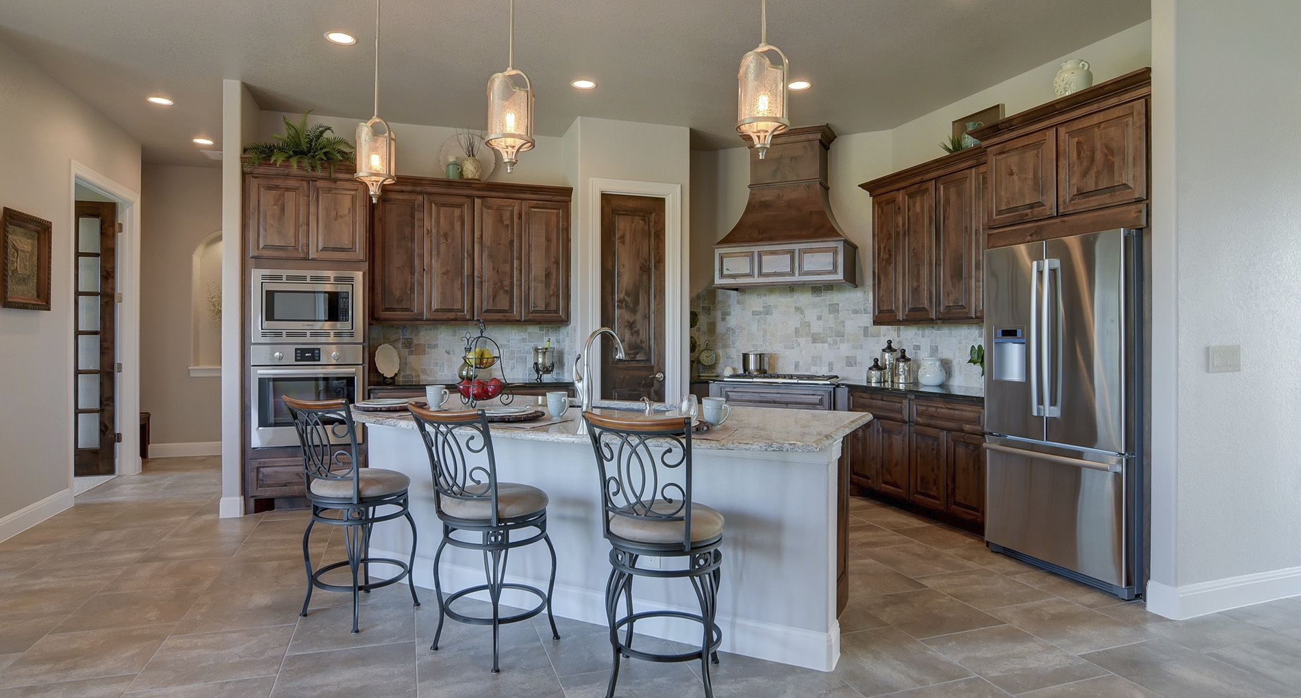 custom kitchen with wood cabinets iron finishing and patterned cream stone backsplash