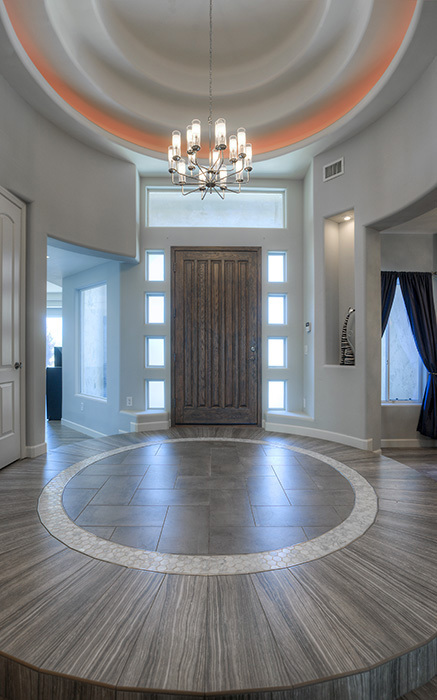 circular entrance with lighting fixture over large wood door