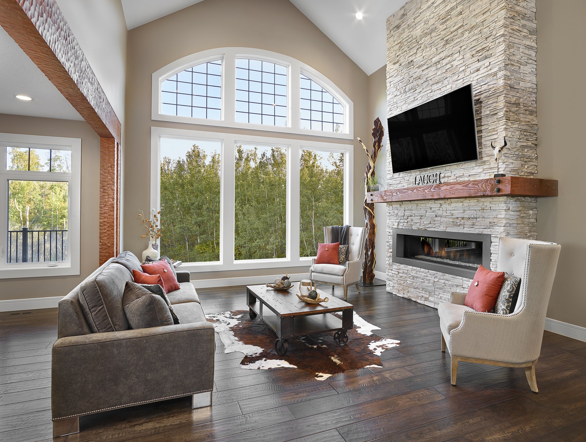 Living area with high ceilings large cream stone fireplace red pillows on neutral colored sofas