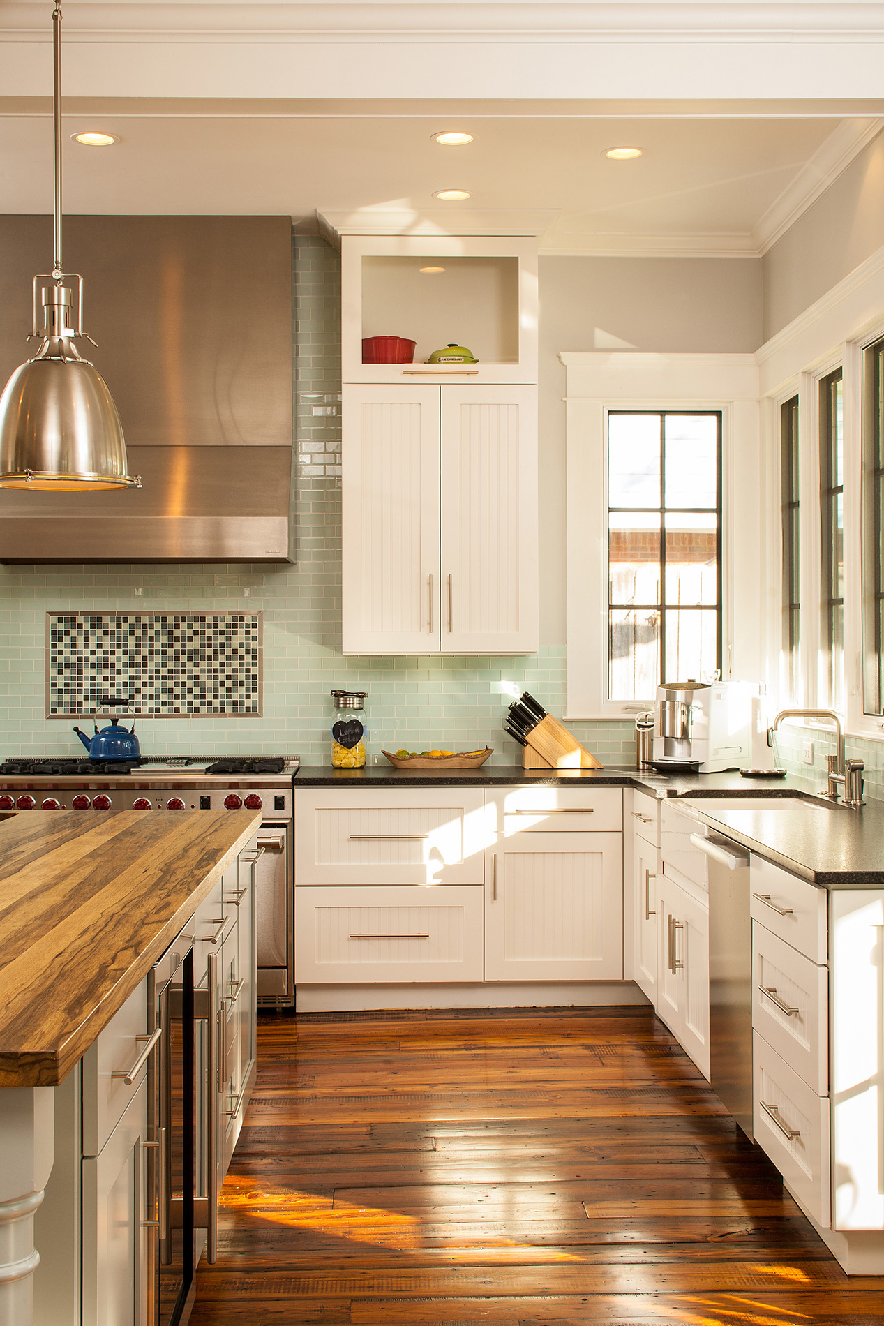Custom kitchen with stainless steel appliances, warm wood top island and geometric backsplash
