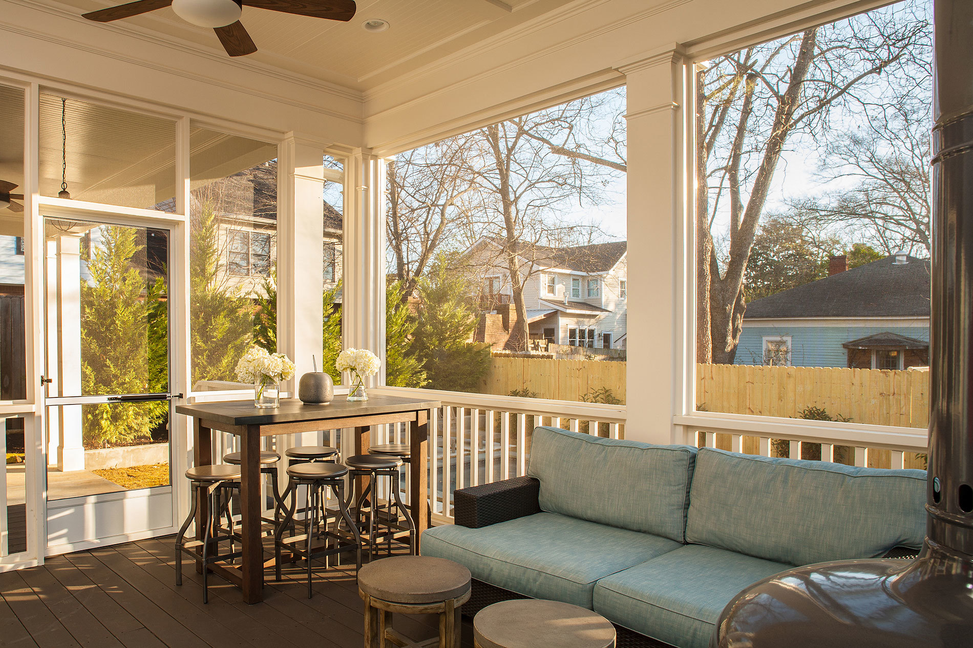 enclosed sun room with blue cushioned couch and small elevated table